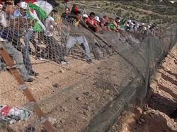 Protesters tear down a barricade in 5 Broken Cameras.