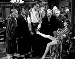 Barbara Stanwyck shows off her assets to Gary Cooper and the seven other professors in Ball of Fire.