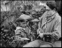 Harold Lloyd teaches a toddler how to roll a cigarette in Billy Blazes, Esq..
