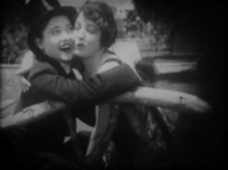 Gloria Swanson in drag cuddles with a woman.