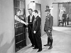 Lew Ayres, in jail, shakes hands with his right hand man, James Cagney in Doorway to Hell.