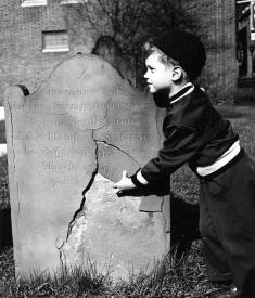 Vivian Maier capturing on film a child vandalizing a tombstone.