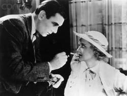 George Brent gives a stylish Bette Davis a light in Housewife.