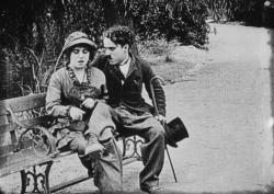 Mabel Normand and Charlie Chaplin on a park bench.