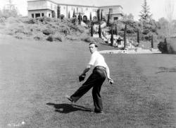 Buster Keaton playing catch on the lawn of his Beverly Hills estate.