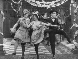 Charles Chaplin dances with two girls in Tango Tangles.