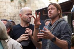 Director Marc Forster seeming to get direction from Brad Pitt during the production of World War Z