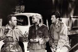 Montgomery Clift, Marlon Brando, and Dean Martin talk during a break in filming The Young Lions.